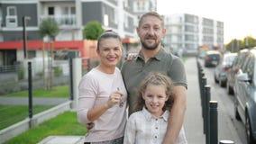 Счастливая семья с детьми стоя на открытом воздухе держа ключи большого загородного дома Усмехаясь роскошные владельцы недвижимос видеоматериал