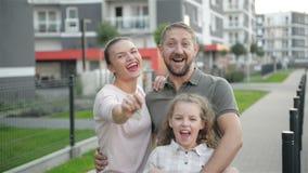 Счастливая семья с детьми стоя на открытом воздухе держа ключи большого загородного дома Усмехаясь роскошные владельцы недвижимос акции видеоматериалы