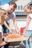 счастливая семья с дочерью подготавливая съесть стоковые изображения rf