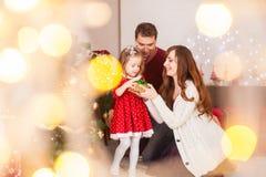 Счастливая семья с дочерью раскрыть настоящий момент на празднике рождества стоковая фотография rf