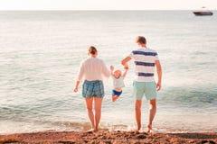 Счастливая семья с младенцем на пляже стоковые фотографии rf