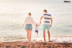 Счастливая семья с младенцем на пляже стоковая фотография