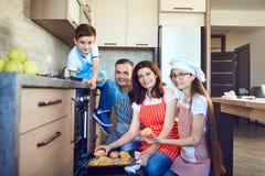Счастливая семья с подносом печенья от печи стоковое фото