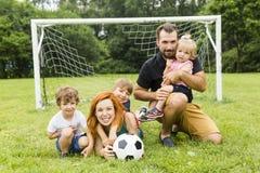 Счастливая семья с шариком футбола на поле стоковое фото rf
