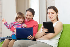 Счастливая семья с электронными устройствами Стоковая Фотография RF