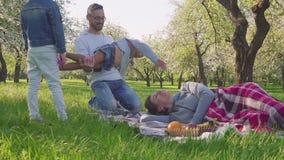 Счастливая семья тратит время на пикнике около blossoming яблони Мать лежит на траве, детях и беге супруга сток-видео