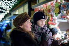Счастливая семья тратит время на ярмарке уличного рынка рождества в старом городке Зальцбурга, Австрии Праздники, концепция Мать  Стоковые Фото