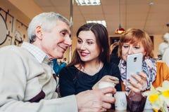 Счастливая семья тратя время совместно Пары семьи Senoir при взрослая дочь используя smartphone в кафе стоковое фото rf