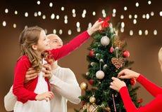 Счастливая семья украшая рождественскую елку дома Стоковая Фотография RF