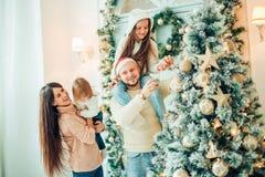 Счастливая семья украшая рождественскую елку с boubles в жить-комнате стоковые изображения rf