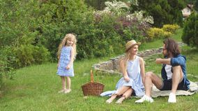 Счастливая семья участвовать outdoors с их милой дочерью, голубыми одеждами, женщиной в шляпе сток-видео