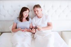 Счастливая середина постарела пары усмехаясь и chating на мобильном телефоне в спальне, людях улыбки стоковые фото