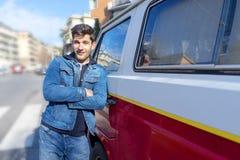 Счастливая склонность молодого человека на ретро мини фургоне стоковые изображения