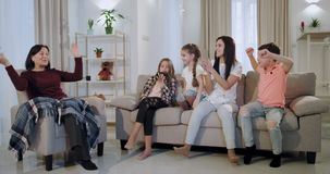 Счастливая смешная бабушка семьи с ее внуками играя на видеоигре перед камерой их усмехаться большой акции видеоматериалы
