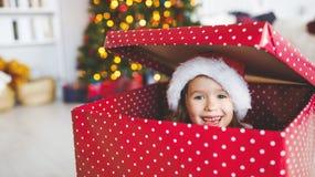 Счастливая смешная девушка ребенка пряча в большом подарке подарка на рождество стоковые фотографии rf