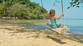 Счастливая смеясь над девушка ребенка отбрасывая на тропическом песчаном пляже стоковые изображения