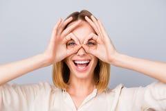 Счастливая смеясь над женщина делая бинокли используя ее руки против g стоковая фотография