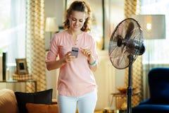 Счастливая современная женщина используя умное домашнее приложение для того чтобы контролировать вентилятор стоковые изображения