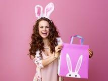 Счастливая современная женщина на розовой показывая хозяйственной сумке пасхи стоковая фотография rf