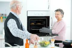 Счастливая созретая микроволновая печь отверстия женщины на кухне Стоковое фото RF