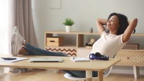 Счастливая спокойная африканская женщина принимая перерыв ослабляя сидит на столе акции видеоматериалы