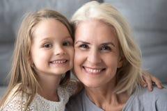 Счастливая старая бабушка обнимая усмехаясь внука смотря пришла стоковое фото rf