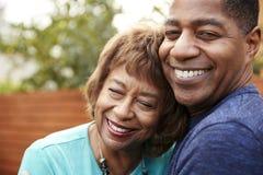 Счастливая старшая Афро-американская женщина и ее средний достигший возраста сын обнимая, головы и плечи, конец вверх стоковые изображения rf
