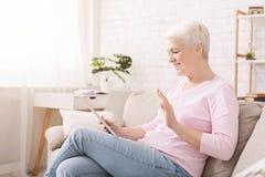 Счастливая старшая женщина разговаривая с семьей через цифровой план стоковое изображение