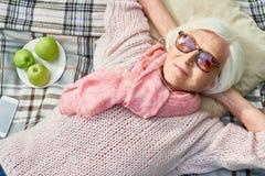 Счастливая старшая женщина слушая к музыке на пикнике стоковая фотография