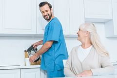 счастливая старшая женщина смотря социальный работника лить горячий напиток в чашке стоковое фото