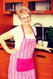 Счастливая старшая женщина стоя в кухне стоковая фотография rf