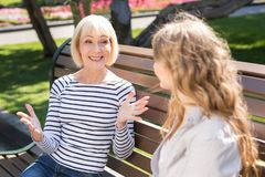 Счастливая старшие мать и дочь сидя на скамейке в парке стоковые фотографии rf