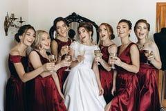 Счастливая стильная шикарная белокурая невеста с bridesmaids на задней части стоковые изображения rf