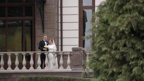 Счастливая стойка пар свадьбы на красивом балконе дворцом видеоматериал