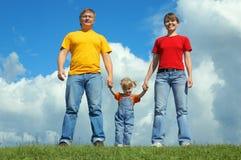 Счастливая стойка семьи на зеленой траве под небом Стоковые Фотографии RF