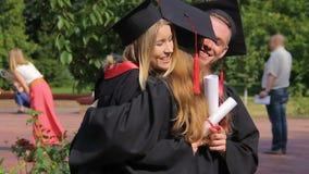 Счастливая студентка поздравляя лучшие други при выпускной день, обнимая видеоматериал