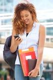 Счастливая студентка смотря мобильный телефон на кампусе стоковое изображение rf