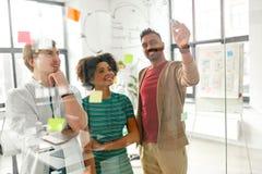 Счастливая творческая команда на доске офиса стеклянной стоковые изображения rf