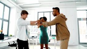 Счастливая творческая команда штабелируя руки на офисе сток-видео