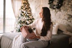 Счастливая темн-с волосами девушка одетая в белых свитере и брюках держит подарок Нового Года в ее руках сидя на кровати с стоковое фото