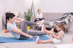 Счастливая тренировка матери и дочери на ковре стоковые изображения