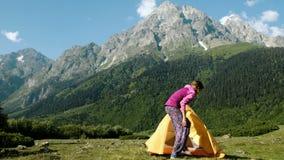 Счастливая туристская женщина раскрывает шатер и сидит внутрь на предпосылке высокой горы на месте для лагеря акции видеоматериалы