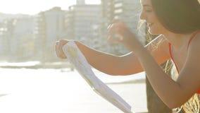 Счастливая туристская проверяя карта в побережье акции видеоматериалы