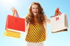 Счастливая ультрамодная женщина показывая хозяйственные сумки против голубого неба стоковая фотография