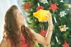 Счастливая ультрамодная женщина с желтой копилкой около рождественской елки стоковые фотографии rf