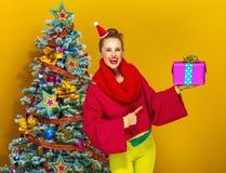 Счастливая ультрамодная женщина указывая на коробку подарка на рождество Стоковое Фото