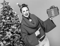 Счастливая ультрамодная женщина указывая на коробку подарка на рождество Стоковые Изображения RF