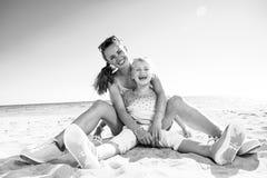 Счастливая ультрамодные мать и дочь сидя на пляже стоковое фото rf