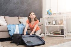 Счастливая упаковка женщины одевает в сумку перемещения стоковое изображение