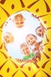 Счастливая усмехаясь группа в составе childs, подросток и взрослые люди смотрят вниз стоковые изображения rf